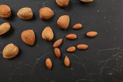 Top down view, almonds, both whole and cracked, on dark marble board.  royalty free stock photography