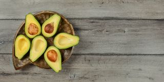Top down view, Avocados cut in half, seed visible placed on old wooden carved bowl and gray wood desk. Space for text on right.  royalty free stock photography