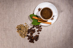 Top down view of beans with hot coffee inside. Top down view on pile of two types of different java beans and herbs beside steaming hot teacup full of coffee and Stock Image
