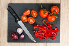Top down view on black cutting board with sliced vegetables stock image