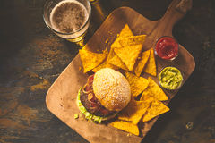 Top down view on burger, chips and beer on table Stock Images