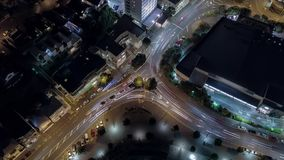 Aerial, Traffic Light Streets At Night Seamless Looping. Top down view of city roundabout, cars traveling around in long exposure to show light trails stock footage