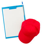 Top down view of clipboard and red cap Royalty Free Stock Photo