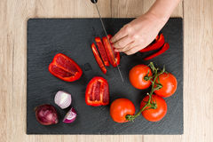 Top down view on cutting board with hands slicing vegetables Royalty Free Stock Photo