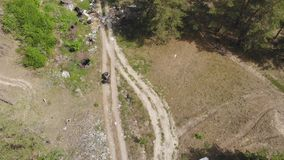 Top-down view of environmental inspector or forester riding atv quadbike through forest polluted with plastic and other
