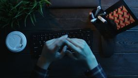 Overhead shot of man drinking coffee and warming up his fingers before typing on keyboard. Top down view of man drinking coffee and warming up his fingers before stock video