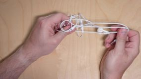 Top down view untangling earbuds. A top down view of a man trying to untangle his earbuds or headphones stock video footage