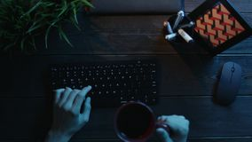 Top down view of man using keyboard and drinking tea. Top down shot of man using keyboard and drinking tea by wooden office table stock video footage