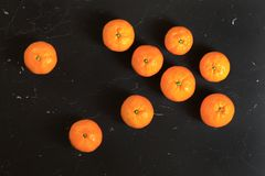 Top down view, mandarines tangerines on black marble board.  stock photos