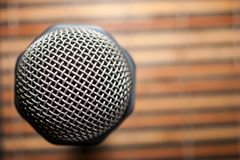 Top-Down View of A Microphone Head and Silver Grille on A Striped Yellow and Black Bamboo Mat Background. Karaoke Bar. Copy Space.  stock photography