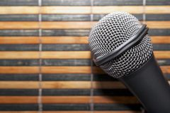 Top-Down View of A Microphone Head and Silver Grille on A Striped Yellow and Black Bamboo Mat Background. Karaoke Bar, Party. Concept. Copy Space stock image