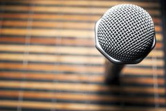 Top-Down View of A Microphone Head and Silver Grille on A Striped Yellow and Black Bamboo Mat Background. Karaoke Bar, Party. Concept. Copy Space stock photography