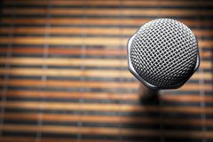 Top-Down View of A Microphone Head and Silver Grille on A Striped Yellow and Black Bamboo Mat Background. Karaoke Bar, Party. Concept. Copy Space royalty free stock image