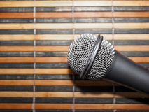Top-Down View of A Microphone Head and Silver Grille on A Striped Yellow and Black Bamboo Mat Background. Karaoke Bar, Party. Concept. Copy Space royalty free stock photography