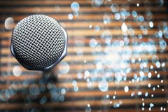 Top-Down View of a Microphone Head on a Striped Yellow and Black Bamboo Mat Background. Round Blue Celebration Soft Lights. Karaoke Bar, Holiday, Festivity royalty free stock photos