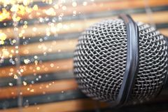 Top-Down View of a Microphone Head on a Striped Yellow and Black Bamboo Mat Background. Round Golden Celebration Soft Lights. Karaoke Bar, Holiday, Festivity stock images