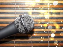 Top-Down View of a Microphone Head on a Striped Yellow and Black Bamboo Mat Background. Round Golden Celebration Soft Lights. Karaoke Bar, Holiday, Festivity stock photo
