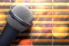 Top-Down View of a Microphone Head on a Striped Yellow and Black Bamboo Mat Background. Round Golden Celebration Soft Lights. Karaoke Bar, Holiday, Festivity royalty free stock images