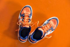 Top down view of orange and white badminton sport shoes on the o royalty free stock photography