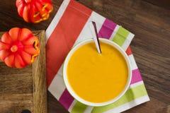 Pumpkin soup. Top down view on simple plain creamy pumpkin soup in green bowl. Seasonal food on striped tea towel Royalty Free Stock Images