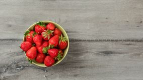 Top down view, small bowl with strawberries on gray wood desk. Space for text on right.  stock photo