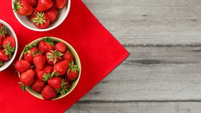 Top down view, small bowls with strawberries, red tablecloth and gray wood desk under. Space for text on right side.  stock photos