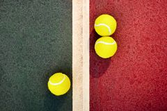 Three yellow tennis balls near the line of a green red concrete. Top down view of three yellow tennis balls on a green and red concrete court divided by a white royalty free stock images