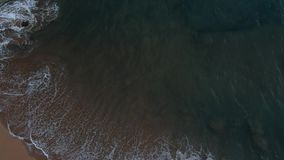 Waves crash on a beach right after sunset stock video footage