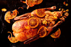 Top down view of whole roasted chicken. Top down view of one roasted whole chicken garnished with lemon fruit slices and stuffed on black background Royalty Free Stock Photo