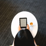 Top down view of woman with e-reader and coffee Royalty Free Stock Photos