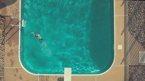 Top down view of young boy jumping off the diving board. A young boy jumps off the diving board into crystal clear blue water during a hot summer day stock footage