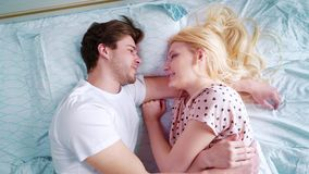 Top down zoom out happy young man and woman in bed in the morning. Loving couple spending lazy weekend together at home. Family, relax and cozy living stock video footage