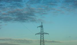 Top of electricity pylon and power lines in front of calm blue evening sky and clouds stock photo