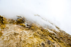 On the top of etna volcano in Sicily. On the top of etna volcano the rock is covered with sulphur and became yellow, cloud of toxic gas spread from the crater Royalty Free Stock Images