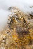On the top of etna volcano in sicily southern italy. On the top of etna volcano the rock is covered with sulphur and became yellow, cloud of toxic gas spread Royalty Free Stock Photos