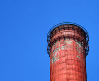 The top of the factory pipes. Top of a shabby red factory chimney smoke-free against the blue sky Stock Images