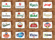 Top famous beer brands and logos. Collection of logos and vector of most popular beer brands and producers on white tablet on rusty wooden background Stock Image