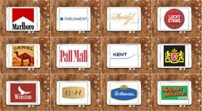 Top famous cigarette brands and logos. Collection of logos and vector of top popular cigarette companies on white tablet on rusty wooden background. brands like Royalty Free Stock Photos