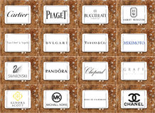 Top famous jewelry companies logos and brands. Collection of logos and brands of most popular jewelry companies on white tablet on rusty wooden background Stock Photos