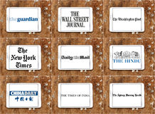Top famous newspaper logos and brands. Collection of logos and icons of top popular newspapers on white tablet on rusty wooden background stock photos