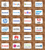 Top famous worldwide technology companies brands and logos. Collection of logos and brands of global technology companies on white tablet on rusty wooden Royalty Free Stock Photos