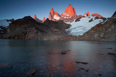 The top of Fitz Roy in pink sunrise and reflections in the lake. Stock Image