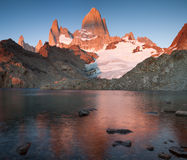 The top of Fitz Roy in pink sunrise and reflections in the lake. Stock Photo