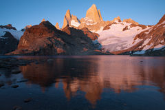 The top of Fitz Roy in pink sunrise and reflections in the lake. Royalty Free Stock Photography
