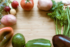 Top flat lay view of fresh organic vegetables. On wooden cutting board with copy space Royalty Free Stock Photography