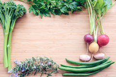 Top flat lay view of fresh organic vegetables. On wooden cutting board with copy space Royalty Free Stock Photos