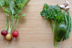 Top flat lay view of fresh organic vegetables. On wooden cutting board with copyspace Stock Photo