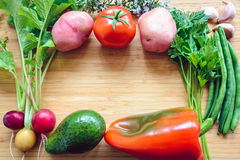 Top flat lay view of fresh organic vegetables. On wooden cutting board with copyspace Stock Images