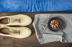 Top flat view of clothing laying on the wooden surface: blue jeans, gray t-shirt, shoes and belt. Casual style. Top flat view of clothing laying on the wooden Stock Image