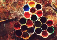 Top flat view of colorful dirty artistic table with color palettes and paint brushes SPECIAL photography EFFECTS. Top flat view of colorful dirty table with stock images